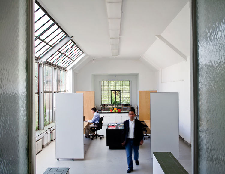 The two-story house is public on the ground level and private on the upper floor. In the office, high bay windows allow northern light to flood the space.