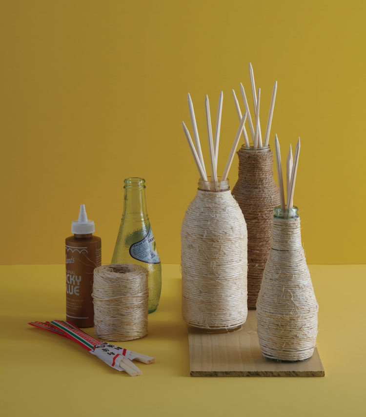 """Pellegrino bottles wrapped in twine become DIY diffusers. """"This project takes advantage of the fact that you can buy little jars of essential oils for reed diffusers instead of buying the whole kit,"""" writes Danny in the book."""