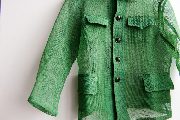 A green mesh shirt designed by Kristen Nakamura hangs from one of Liu's white walls.