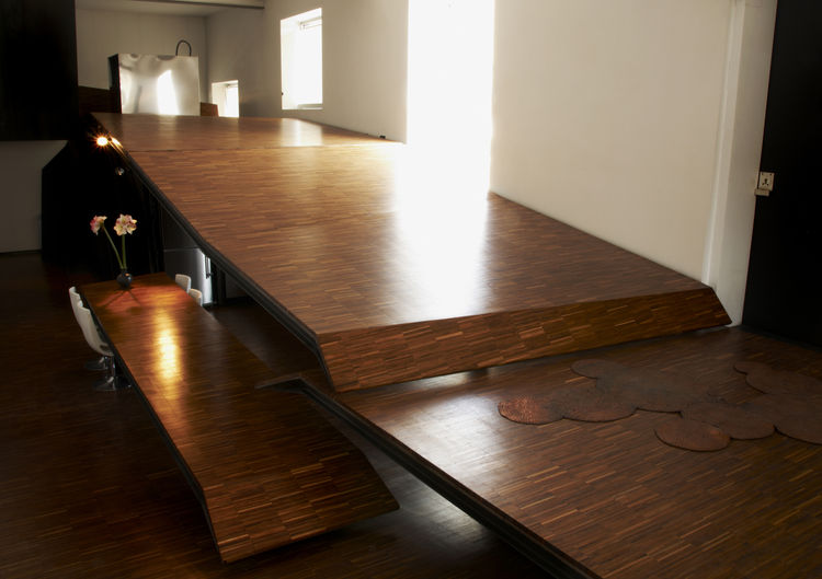 Cormier designed a movable parquet ramp that leads to the sleeping loft and masks his kitchen.