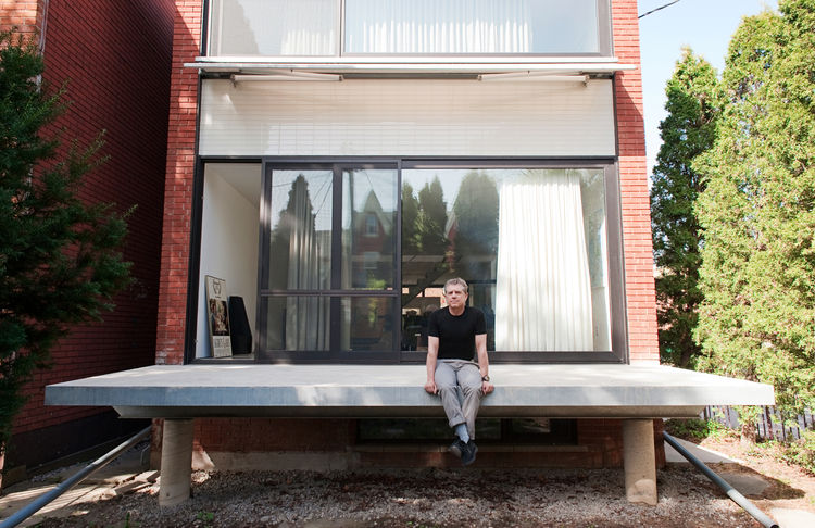 Martin Kohn, principal of Kohn Shnier Architects, sits atop the cantilevered porch of the Brookfield House.