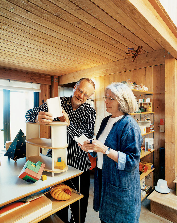 In the living room of their home at The Sea Ranch, Maynard Hale Lyndon and Lu Wendel Lyndon examine LyndonDesign's new shelving system. Next to the system sits Maynard's prized Cubicus by Peer Clahsen.