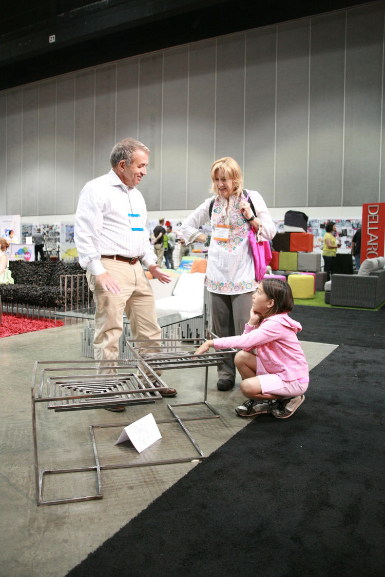 "A trio ponders the merits of an angular metal side table, just adjacent to the <a href=""http://www.dwell.com/articles/preview-modern-family-zone.html"">Modern Family Zone</a>. Remember, kids under sixteen get into Dwell on Design for free!"