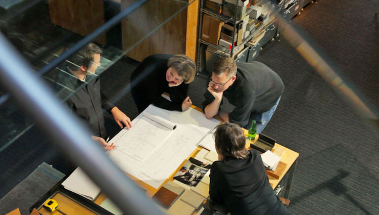 Edward LaLonde reviews the elevation drawings for the kitchen while the rest of us look on. We are surrounded by bookshelves stocked with every imaginable swatch or sample. Tom and Edward are able to quickly grab samples to illustrate their ideas.