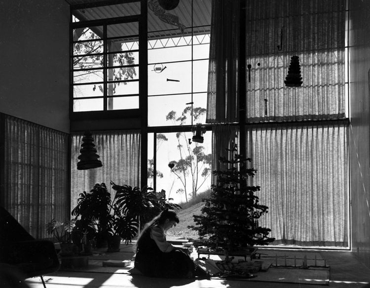 "Ray Eames in the Eames House living room, Christmas 1949. The couple moved in on Christmas Eve with very little and furnished the home slowly over the ensuing decades. Photo courtesy <a href=""http://eamesfoundation.org/"">the Eames Foundation</a>."
