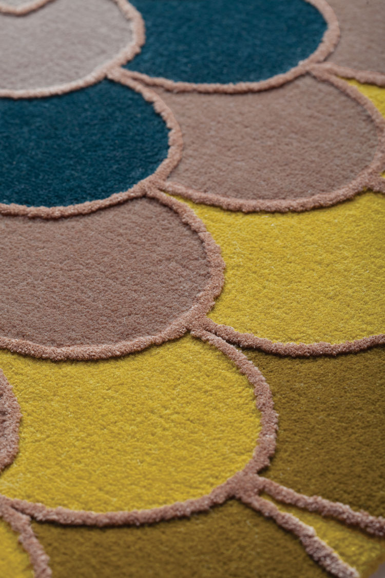 Raised scalloped edges articulate the rich dyes in the wool and silk rug.