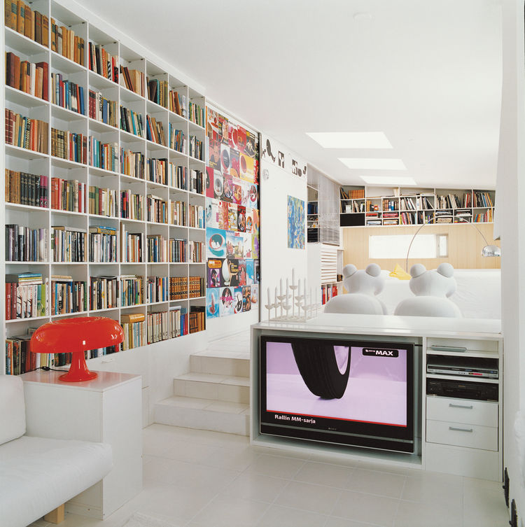 The Aarnios' living room includes a wall of magazine covers featuring the designer's work and a pair of white Pony chairs, Aarnio's 1973 design.