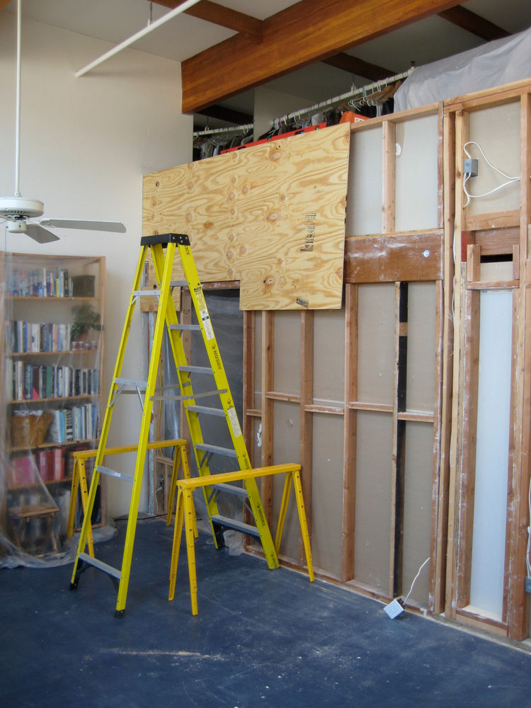 Once we removed drywall on the living room side, I laid up sheets of plywood—all by myself. I had to do this choreographed sequence of getting the board onto the sawhorses, dead lifting it up onto some temporary nails in the studs, climbing the ladder whi
