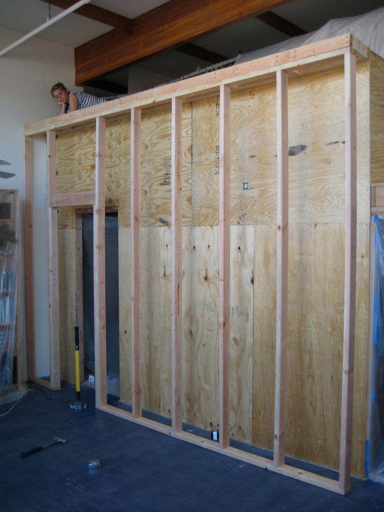 This shot shows the bookcase framing up. I built a regular wood-stud wall and spaced it off of the plywood with a narrow deck at the top. The wood bookcase cladding went in and out and wrapped each of the stud bays. I did some basic rough electrical wirin