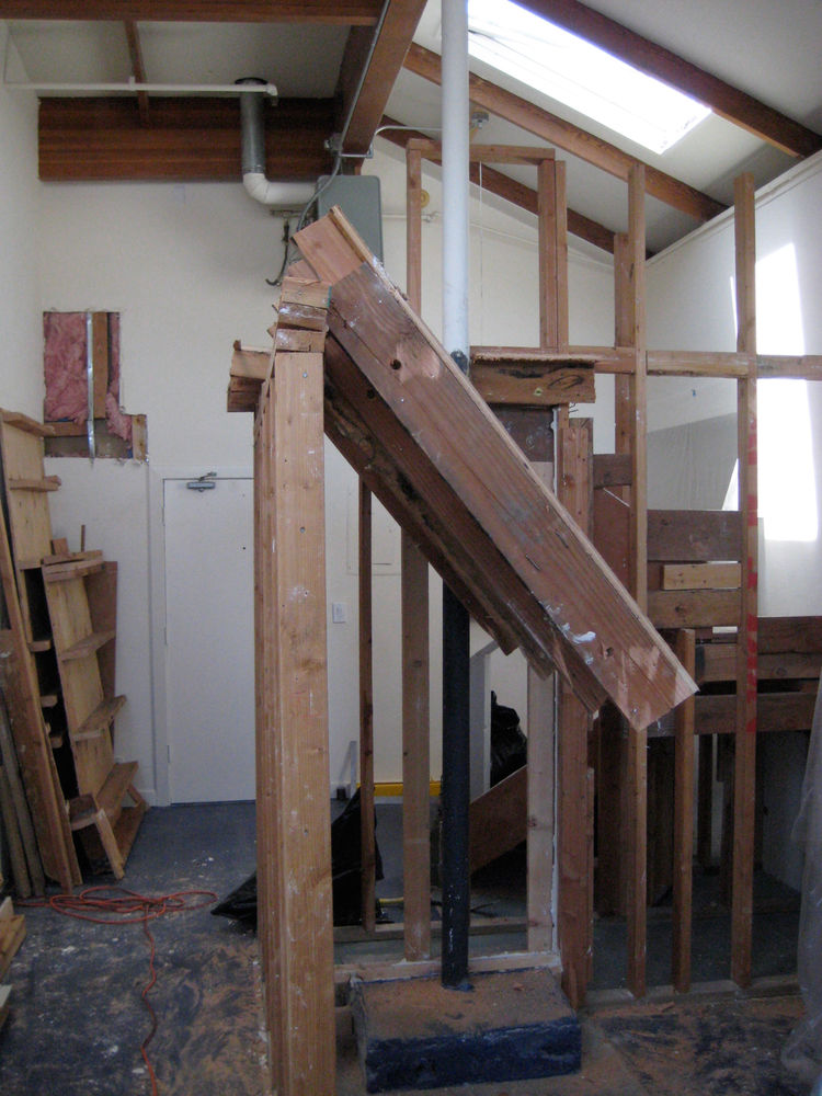 This shot shows the existing loft, halfway down. It was mostly all framing with a little bit of electrical wiring so it came down pretty easily with the sledgehammers—but it was a total mess. I had to pull the deck down myself, which was tricky; I ended u