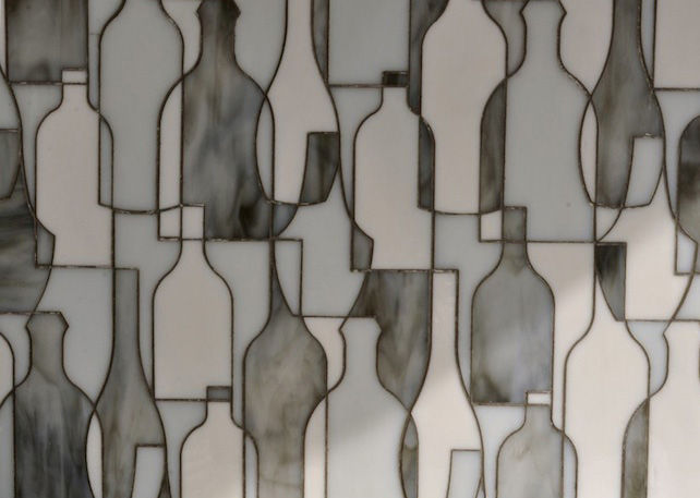 "A longtime tile designer, Erin Adams began to work on a collection for New Ravenna in 2011. She seeks to develop patterns not usually seen in tile, like her abstract ""Bottles"" design."