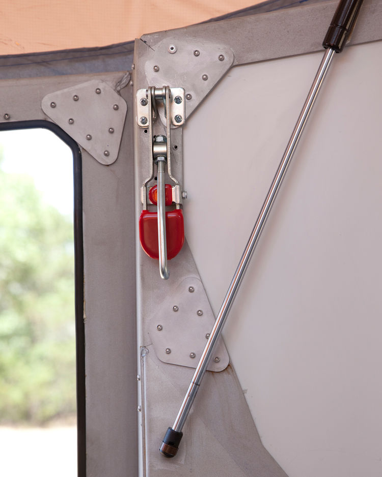 Hooks on the inside (like the mechanism with the red tab) latch into the camper's roof to help hold it down. Throughout the camper, small cricket images are laser-cut into the aluminum frame. The camper's name hints at its shape and is meant to conjure vi