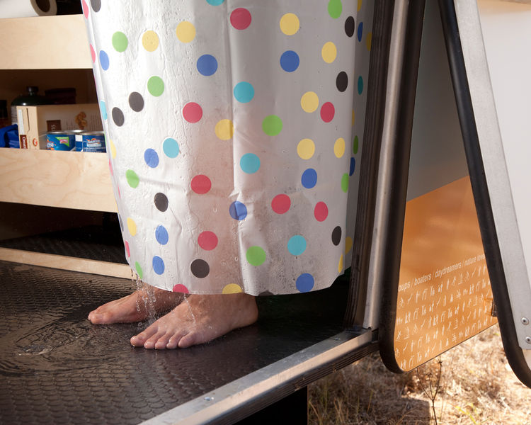 The handheld shower is intended for rinsing off muddy feet and pets rather than giving yourself a full-fledged scrub. Although you can use it inside the trailer (the shower curtain and floor drain will keep most of the water from splashing all over), it's