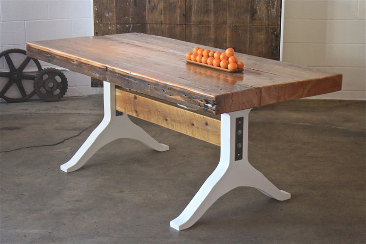 """One of McGowan's favorite pieces is this dining table. """"We found a 4.5-inch-thick old growth pine beam that was once used to support an 1800's building. We mounted it on white lacquered MDF legs to draw tension between the overly thick top and the glossy"""