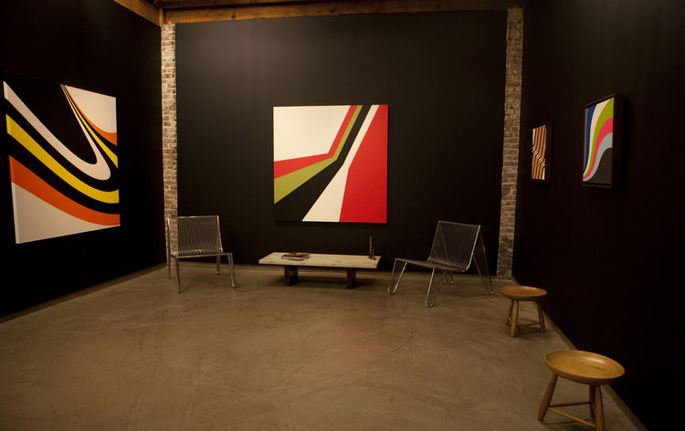 From left, <i>Süfnex</i>, 2004 and <i>Stryyka</i>, 2006, hard-edge paintings by Grant Wiggins, with prototype INOX Poltrona Moeda chairs by Zanini de Zanine Caldas. Photo courtesy Elko Weaver.