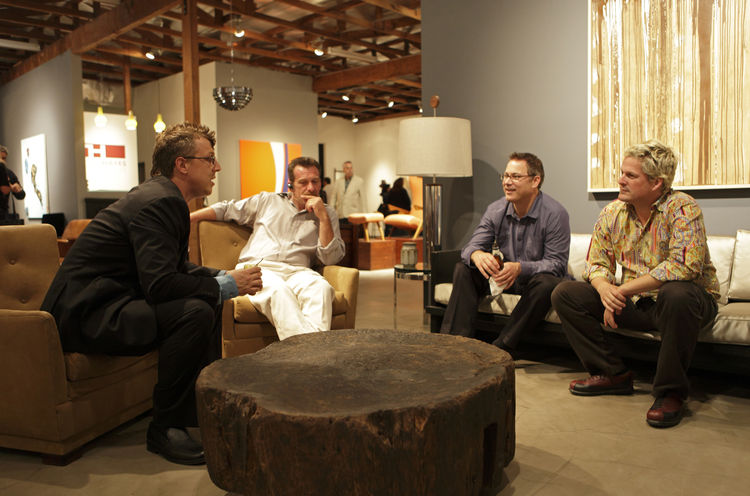 Hayes, left, and visitors around a 1940s solid peroba wood table from Brazil. Photo courtesy Elko Weaver.