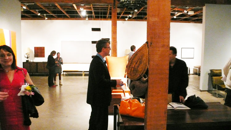 Thomas Hayes, center, on opening night. At rear is <i>Memorabilious</i>, 1972, a color field painting by Donald Kaufman; at right is a sketch by Oscar Niemeyer.