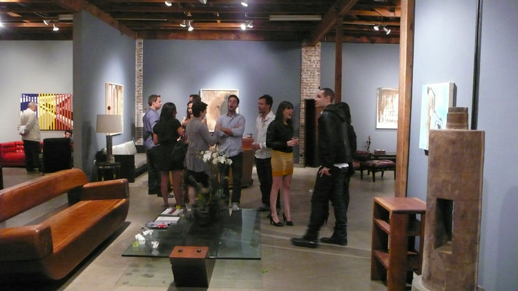 Gallery visitors near a reclaimed ipe wood sofa and cantilevered glass table, foreground, by Zanini de Zanine Caldas.