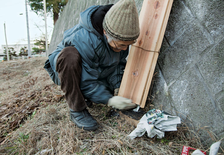 Fujimori, demonstrating the process of charring cedar boards, packs newspaper into the base of three planks that have been bound together.