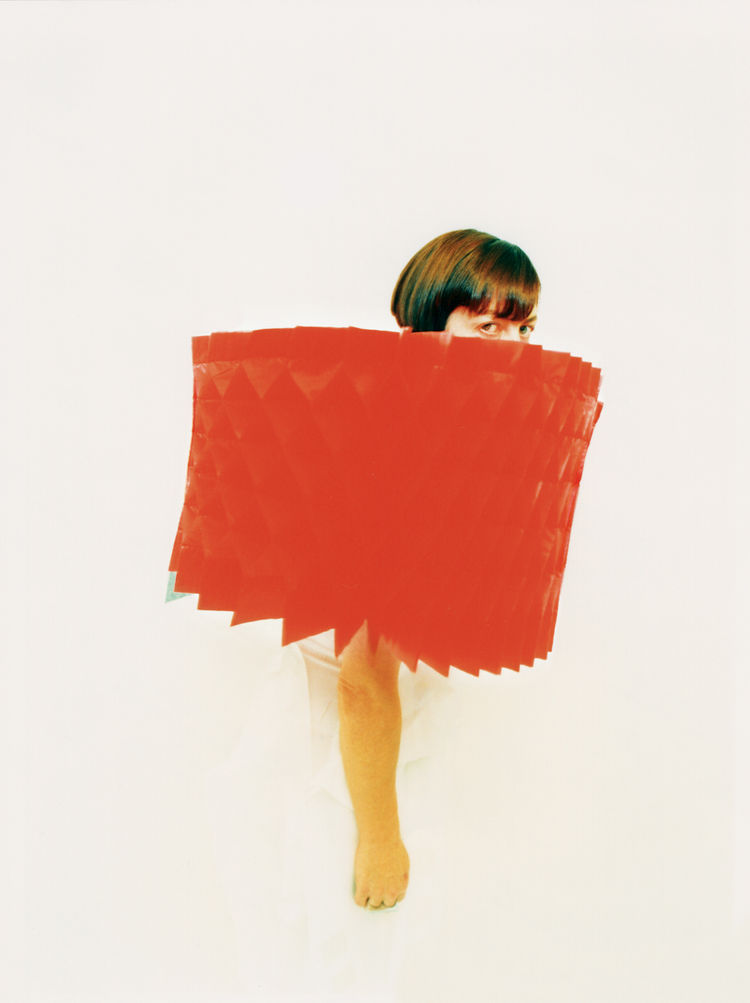 This image is of a red polyester cap by Hiroaki Ohya is from the Spring/Summer 2000 Wizard of Jeans collection. The cape expands like a beehive and can also be folded flat.