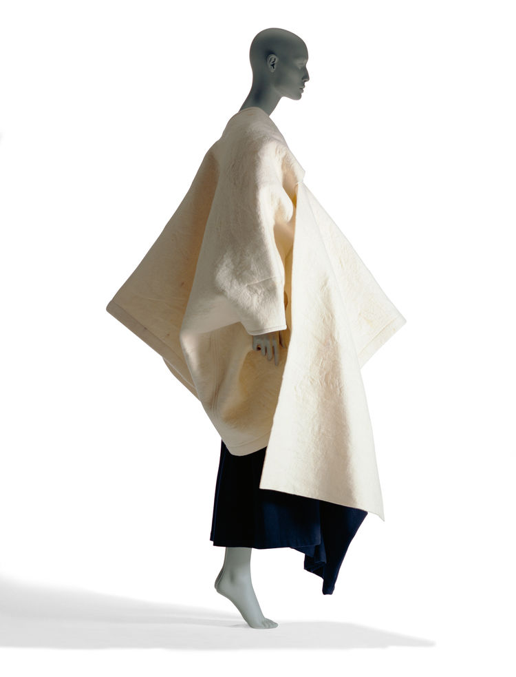 This coat from Rei Kawakubo's 1983-1984 Autumn/Winter collection for Comme des Garcons is made of wool felt. Though it has a strong, sculptural form when worn, it's actually made of two panels, the smaller of which slides through a slit in the larger piec
