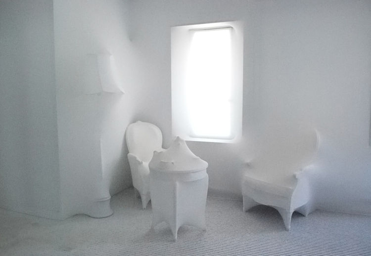 Although the furniture is still evident, the absence of color renders this blanched corner with a phantom-like, three-dimensional surrealist effect.