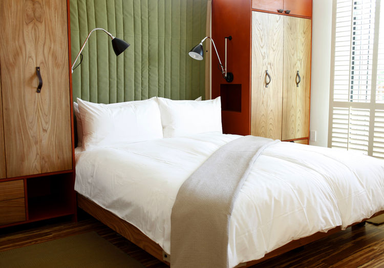 The 36 guest rooms have floor-to-ceiling wood shutters, custom elm beds, and built-in armoires whose internal LED lamps light upon opening, like a refrigerator. Quilted headboard hangings soften the room without taking up space, are easily cleanable, and