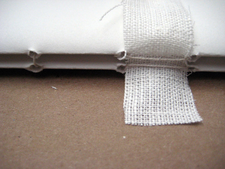 Line up the next signature on top of the first. You'll sew this one in the opposite order of the first; so it's in the last hole, out the fifth, in the fourth, out the third, in the second and out the first. Take care to keep the strips of cloth between h