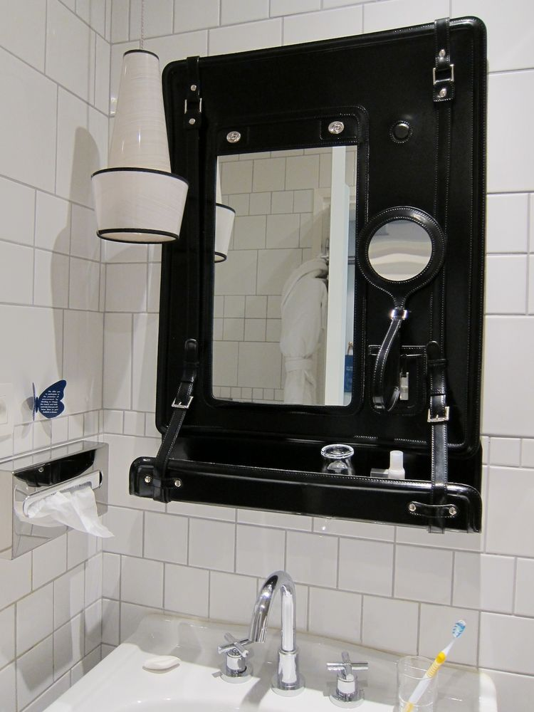 The defining feature in the bathroom was this custom black leather mirror, modeled on a vintage traveling set for safari-goers. All the straps and hardware gave it a vaguely bondage-y look—but it was also quite practical, with a built-in shelf and magneti