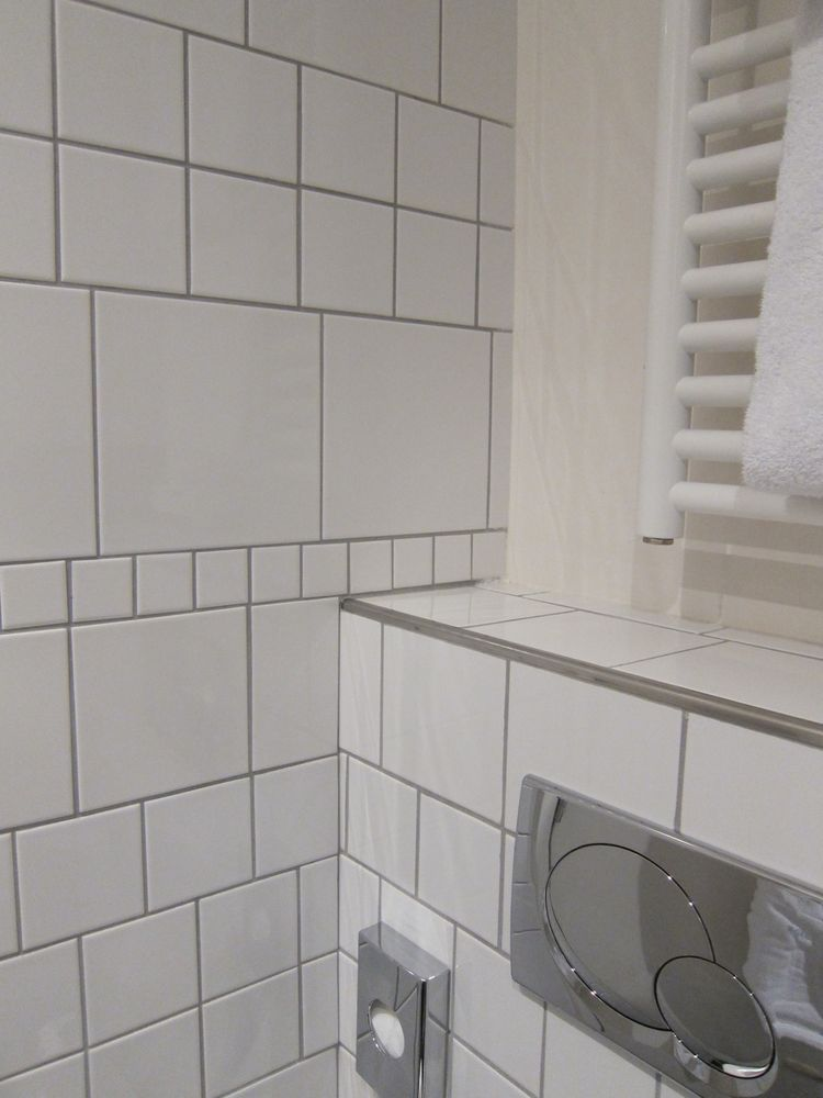 Another clever design move: To create visual interest and texture on the walls in a smart, affordable way, Auer mixed together four standard sizes of basic white bathroom tile, alternating their scales and staggering alignment.