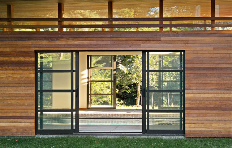 Sliding glass doors open to reveal the interior of the pool house, which boasts a line of clerestory windows just below the roof.