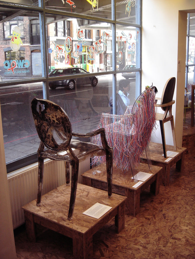 A trio of chairs on display in the window.