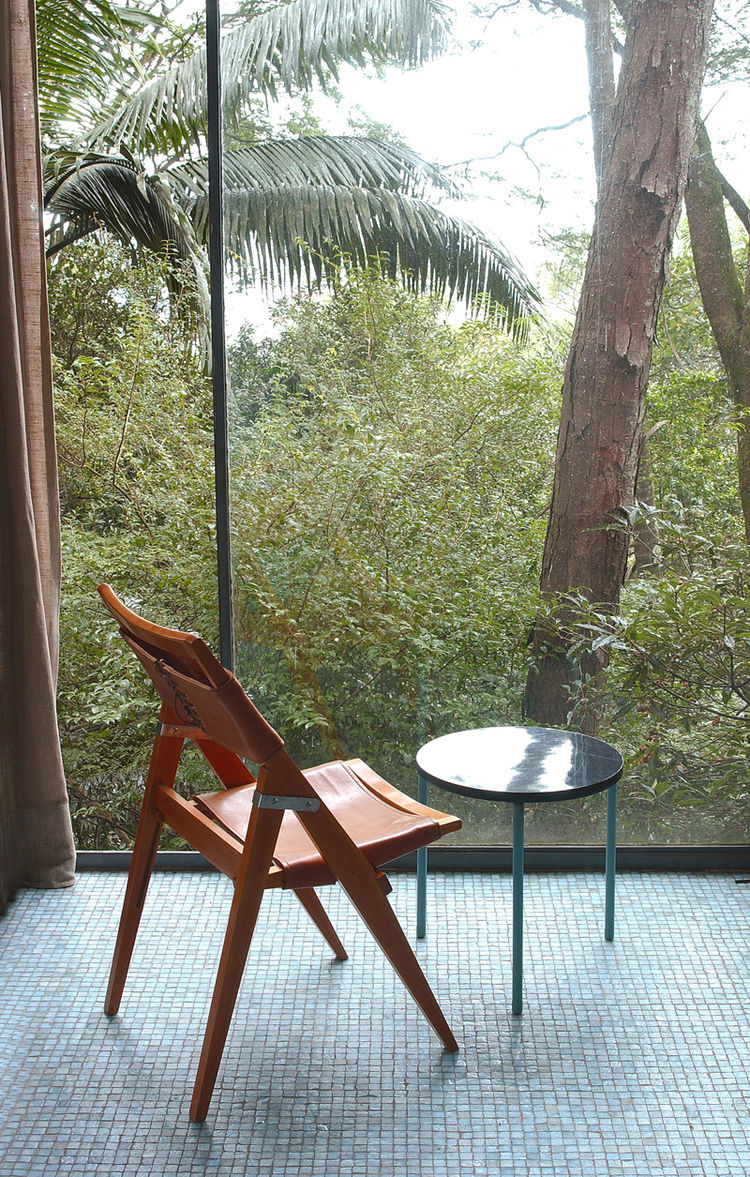 """Her folding side chair, against the floor-to-ceiling window wall of the Glass House. Photo courtesy <a href=""""http://espasso.com/"""">Espasso</a>."""