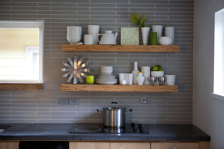 Dishes rest atop a shelf made from a type of textured lumber typically used for framing. The horizontal tile behind the shelf echoes the pattern and proportion of the bricks used in the hearth. <br /><br />Michelle and Cameron did nearly all of the work t