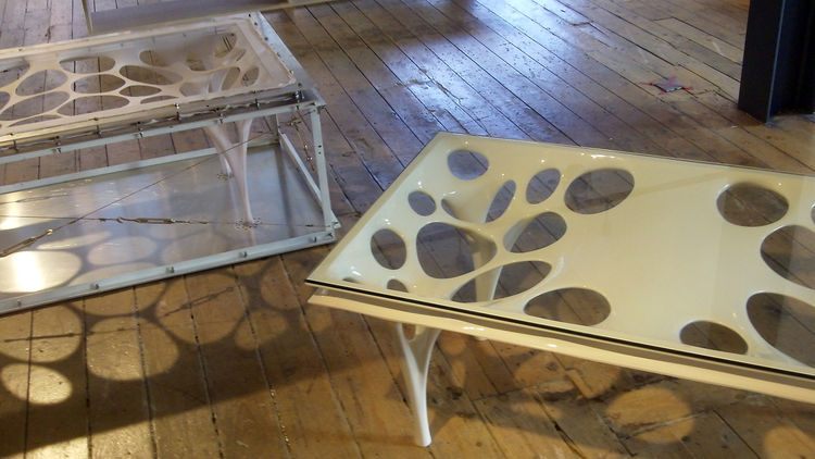 A coffee table designed by Il Hoon beside the machine-like mold used to create its elastic forms.