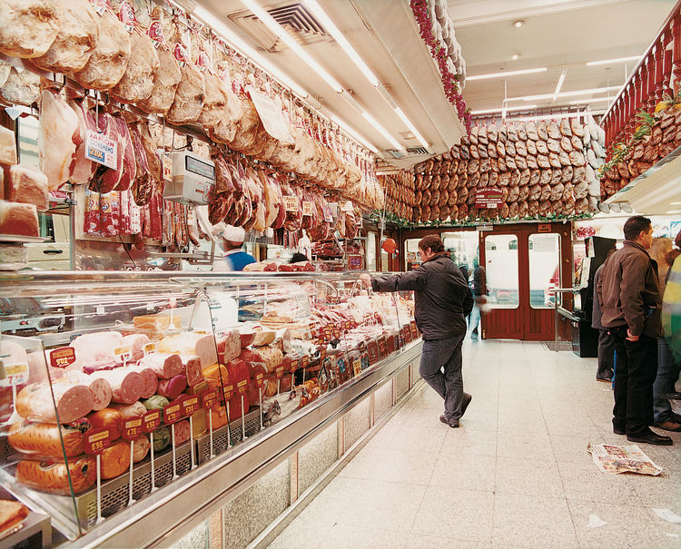 Cured ham hocks dangle from the ceiling of Museo del Jamón, celebrating Spain's famed Serrano ham culture.