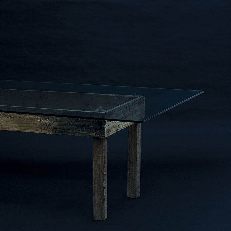 The Abuletada is a dining table with a glass top attached to a humble wooden base.