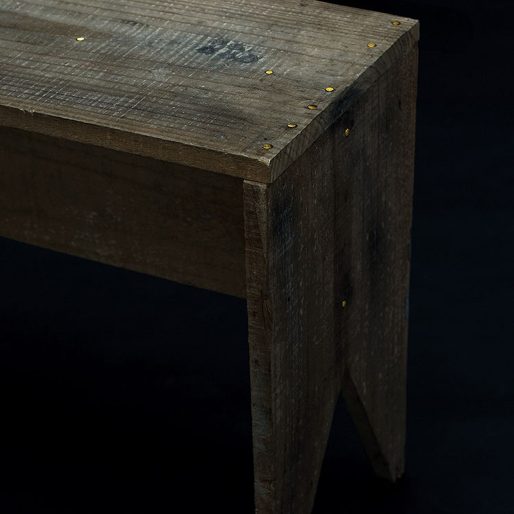 In a truly alchemical mixture of high and low, this bench-table is fashioned with golden nails.