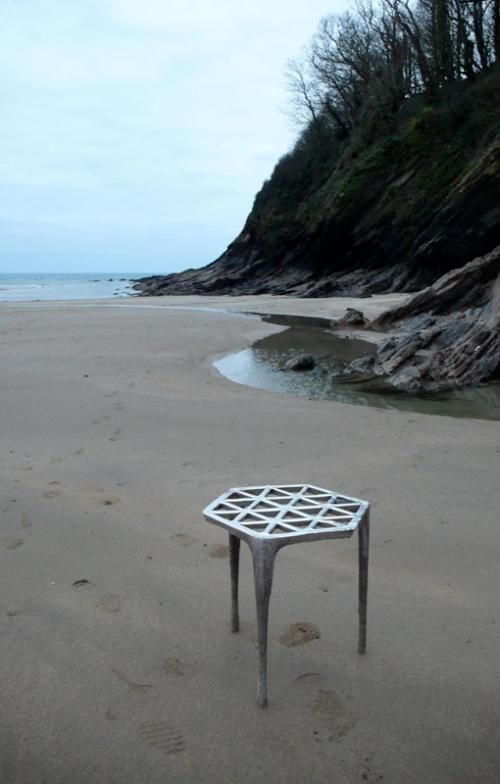 Max Lamb's pewter stool is cast from a formwork of wet sand on the beaches of Cornwall, England.  After digging the three legs and hexagonal structure plate into the sand, he poured molten pewter into the mold cavity, and when it set, dug out the stool. (