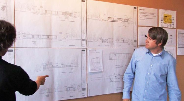 Tom Kundig (left) and Edward Lalonde (right) tag team on the project overview, pointing out various features of the project. At the beginning of the critique, Tom and Edward pose specific questions to the firm to help frame the entire discussion.