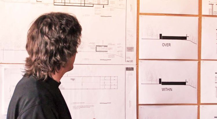 Here, Tom Kundig reviews the general layout of the house. Oversized plans are pinned on the wall so everyone can follow along, and even make notations right on the documents themselves.