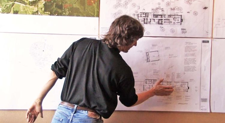 Tom Kundig gestures towards the private and public areas of the residence. To provide context, he walked the firm through the design of the house and the overall design concept and rationale. He spoke about how the house would address the slope and view t