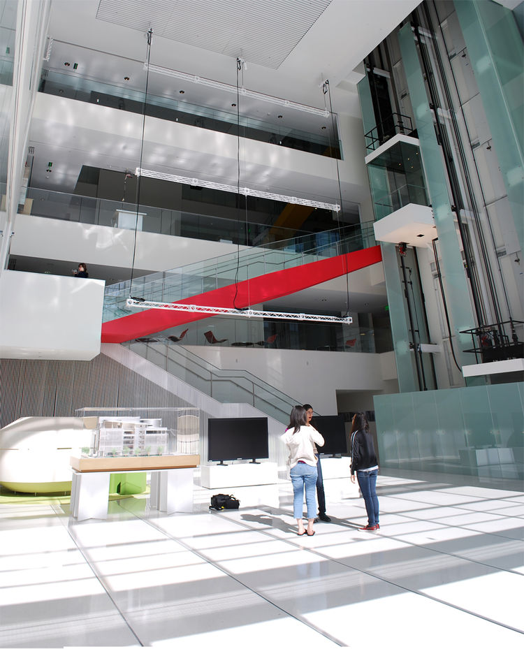 The main atrium in the center is pierced by two glass elevators and a red staircase. As I descended to the first floor, I noticed that the stairs were carefully calibrated to be just too far apart to walk down normally, so I was forced to somehow half-run