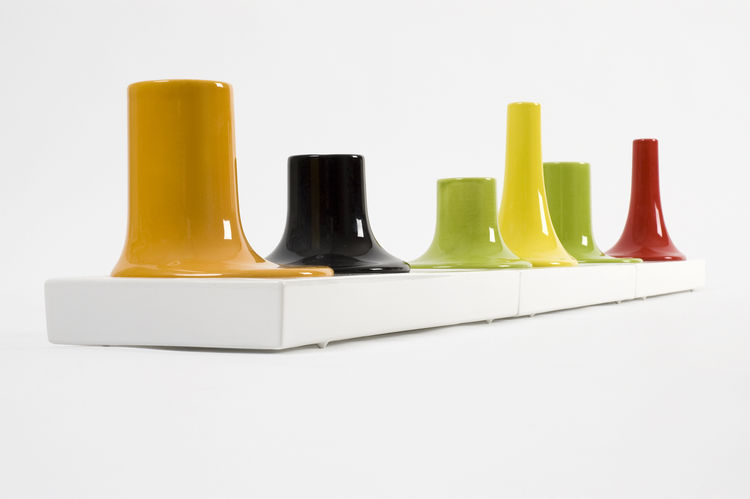 Bosa, Venini, Laboratorio 2729 all collaborated to create the ceramic candle holders of Luca Nichetto's Essence Cinque series. The modular items in the slick, colorful collection is meant to evoke the shape of pieces created by being poured into a mould.
