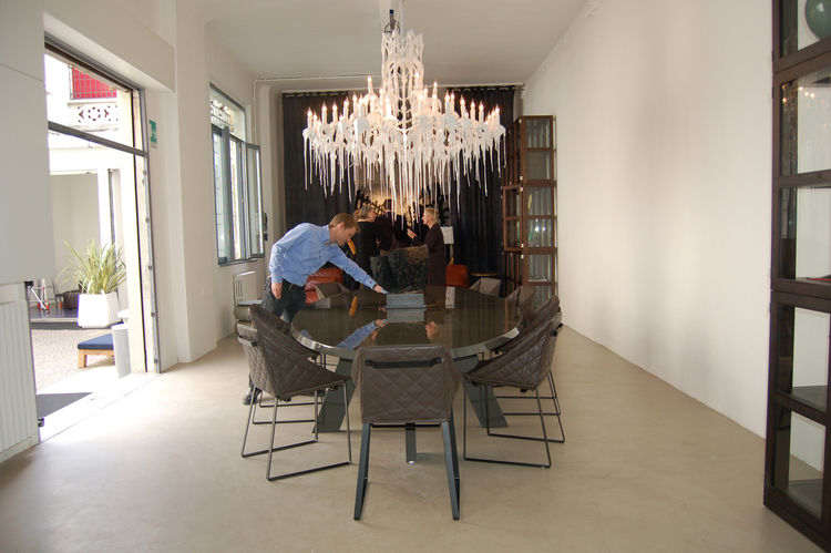 Inside the dining area, Piet Boon's tufted leather Kekke chairs surround a highly polished stone table. His Hot Kroon chandelier, which is dipped in half-melted plastic, hangs above.