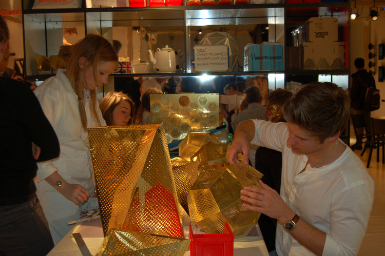"Inside <a href=http://www.tomdixon.net/home"">Tom Dixon</a>'s booth, a group of Flash Factory workers assemble the perforated-brass Etch lamp in real time; the pieces are available for purchase on-site."
