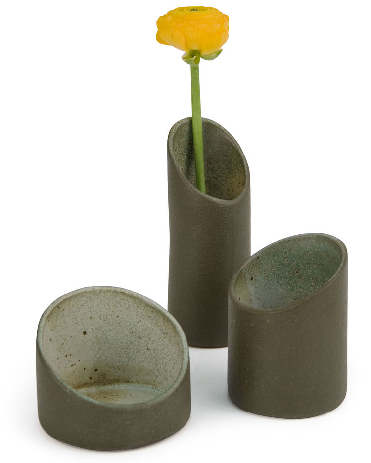 These cylindrical nesting vases are inspired by the shape of bamboo. Though made from ceramic, the surfaces have a roughness that evokes forests or jungles. They come as a set of three and can be stacked and used as a single vase, or separated and arrange
