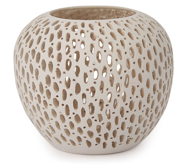These intricately detailed oval-shaped candleholders are made by hand from Brazilian white clay. When a tea light is lit inside, the openings in the surface of the candleholder cast patterns and shadows on the wall round it. MoMA Exclusive. Small Oval: 2