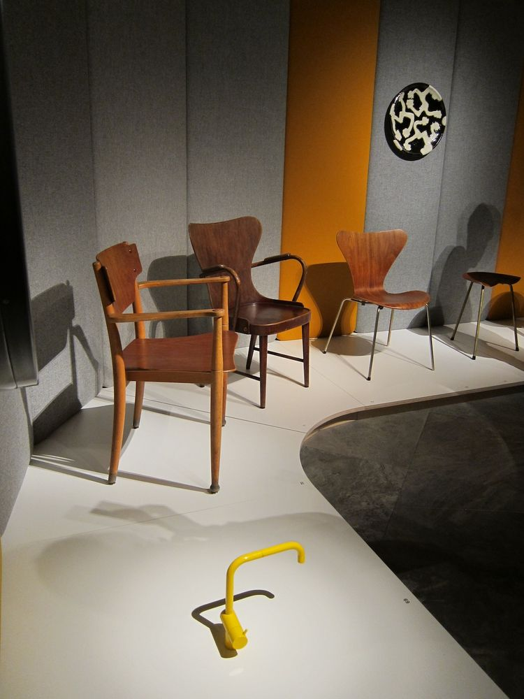 In one corner of the show, a bright yellow Vola faucet, designed by Arne Jacobsen and Teit Weylandt in 1969, holds court with a tribe of wooden chairs from the 1940s and 50s.
