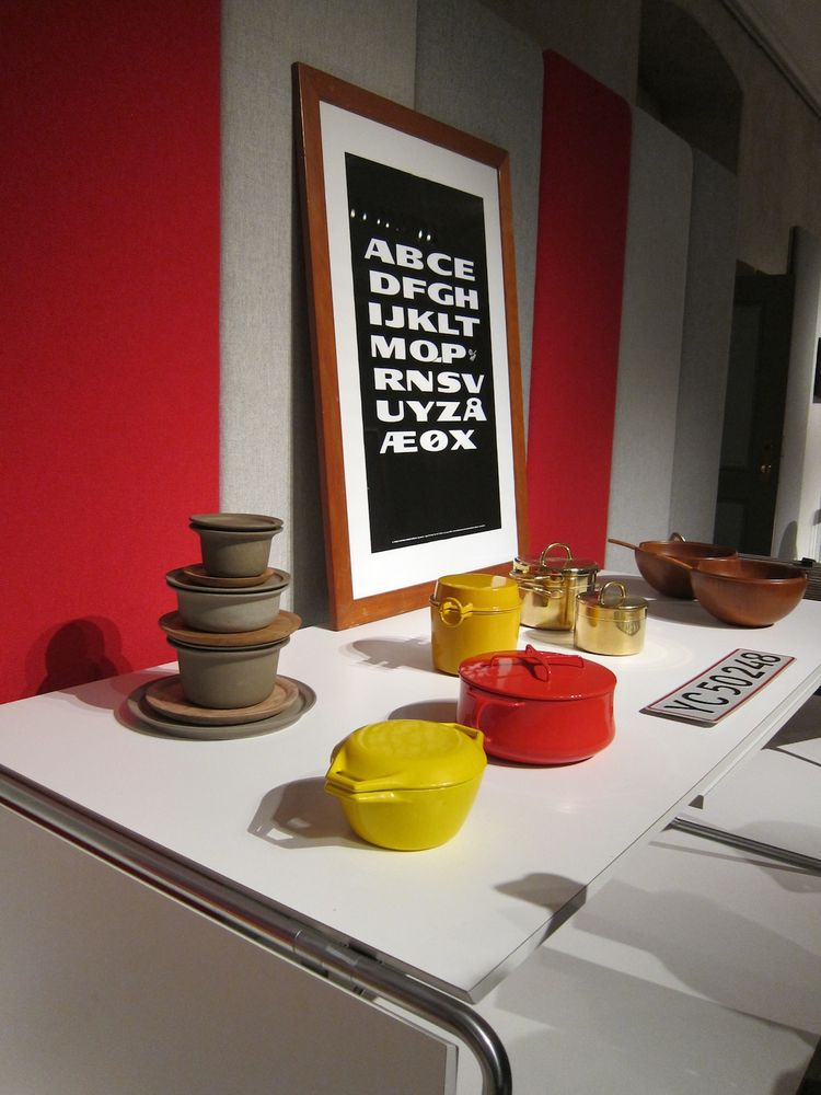 In the foreground, a red Kobenstyle and yellow Orecast pot, designed by Jens Quistgaard in 1954 and 1959, respectively, with an alphabet poster in the background by Claus Achton Friis.